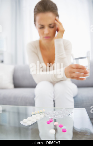 Closeup on pills and feeling bad young woman in background - Stock Photo