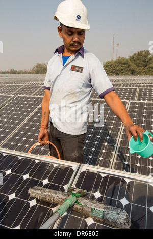 Workers washing the dust off solar panels at a 1 MW solar power station run by Tata power on the roof of an electricity - Stock Photo