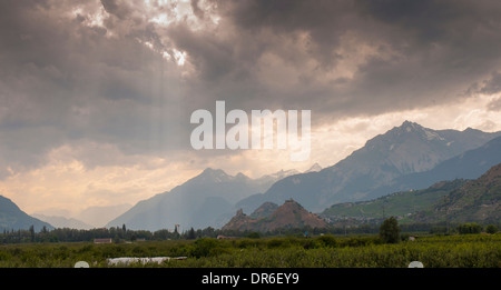 Dramatic sky over the mountains and town of Sion in the Rhone valley in Switzerland, taken from the cycle path along - Stock Photo