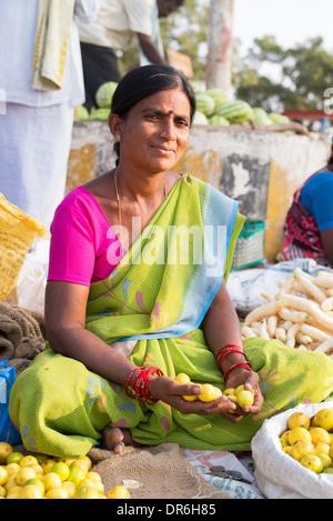 Indian women selling lemons at a street market in Puttaparthi, Andhra Pradesh, India - Stock Photo
