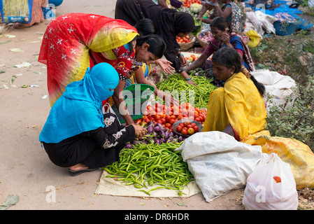 Indian women buying vegetables from a street market in Puttaparthi, Andhra Pradesh, India - Stock Photo