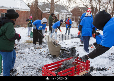 Detroit, Michigan USA - Volunteers from Wayne State University clear debris and board up vacant houses near Cody High School on the Martin Luther King Jr. holiday. Here they clean up the remains of a burned-out garage. Credit:  Jim West/Alamy Live News