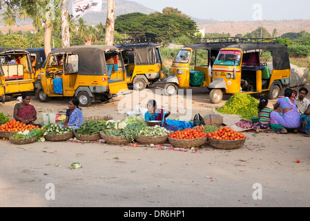 Indian women selling vegetables from baskets at a street market in Puttaparthi, Andhra Pradesh, India - Stock Photo