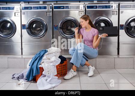 Woman Enjoying Music In Laundry - Stock Photo
