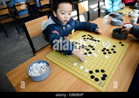 Xining, China's Qinghai Province. 21st Jan, 2014. Bai Yifan, a seven-year-old boy, plays weiqi, or go, at a youth - Stock Photo