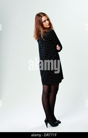 Rear view portrait of a young beautiful woman on gray background - Stock Photo