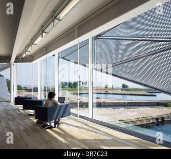 Interior view of The Culture Yard, Library, Elsinore, Denmark. Woman sitting working on lap top - Stock Photo