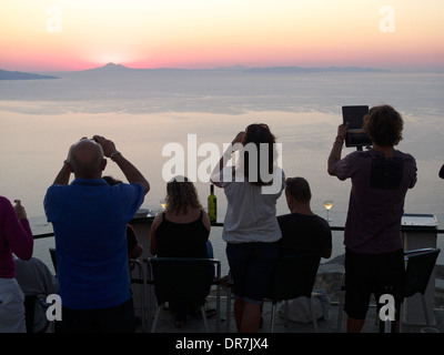 europe greece cyclades sikinos tourists taking a picture of the sunset - Stock Photo