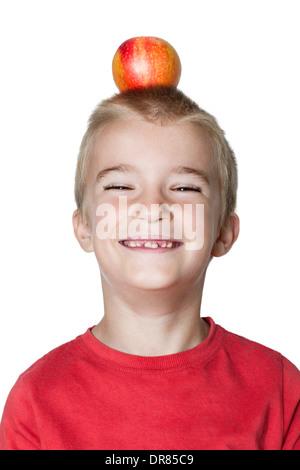 Portrait of boy (6-7) having apple on head. - Stock Photo