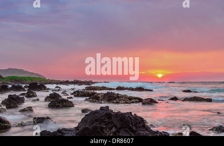 Intensely colorful sunrise over the ocean at Sandy Beach in Oahu, Hawaii - Stock Photo
