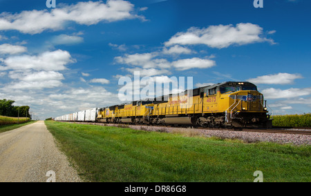 Lincoln Highway gravel road alongside the railroad tracks where the Union Pacific train is running near to Ashton, - Stock Photo