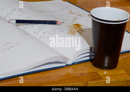 Hot drink liquid knocked over on to pages of work book. - Stock Photo
