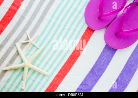 Beach scene with purple flip flops and two starfish on a striped beach towel. - Stock Photo