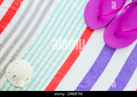 Beach scene with purple flip flops and a sand dollar on a striped beach towel. - Stock Photo
