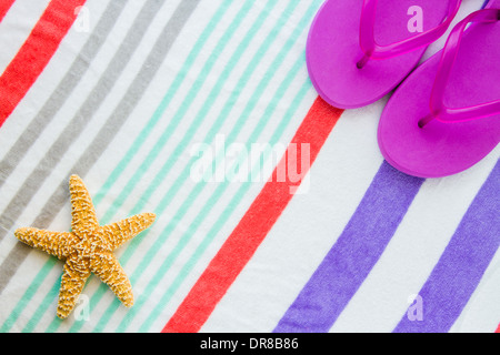 Beach scene with purple flip flops and a starfish on a striped beach towel. - Stock Photo