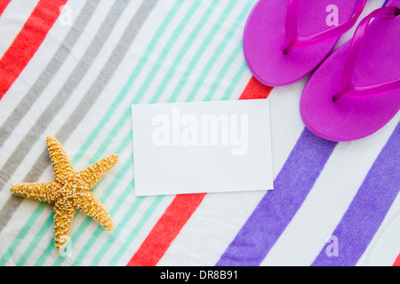 Beach scene with purple flip flops and a starfish on a striped beach towel with copy space. - Stock Photo