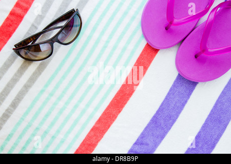 Beach scene with purple flip flops and sunglasses on a striped beach towel. - Stock Photo