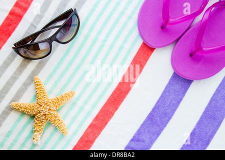 Beach scene with purple flip flops, sunglasses and a starfish on a striped beach towel. - Stock Photo