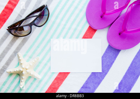 Beach scene with purple flip flops, a starfish, and sunglasses on a striped beach towel with copy space. - Stock Photo