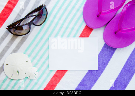 Beach scene with purple flip flops, sand dollars and sunglasses on a striped beach towel with copy space. - Stock Photo