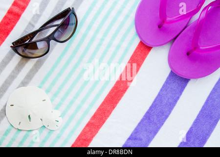 Beach scene with purple flip flops,sand dollars and sunglasses on a striped beach towel. - Stock Photo