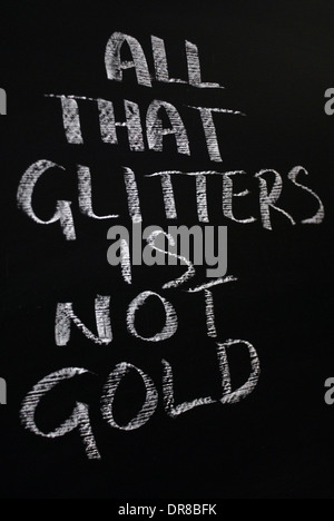 chalk writing- All that glitters is not gold.- words written on a blackboard. - Stock Photo