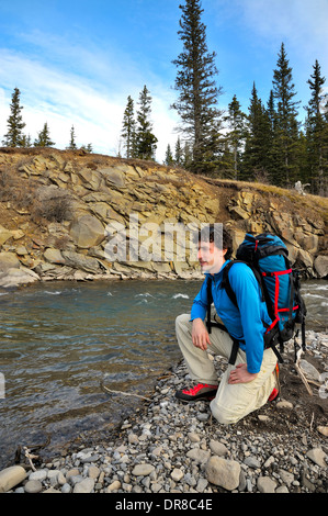 A hiker stops to rest along a fast flowing stream in the foothills of the rocky mountains of Alberta Canada. - Stock Photo