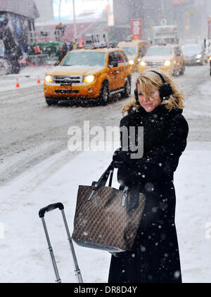 New York, NY, USA. 21st Jan, 2014. A pedestrian waits in snowstorm for signal to pass a street near the Times Square - Stock Photo