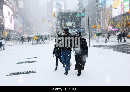 New York, NY, USA. 21st Jan, 2014. Pedestrians walk in snowstorm across the Times Square in New York City, the United - Stock Photo