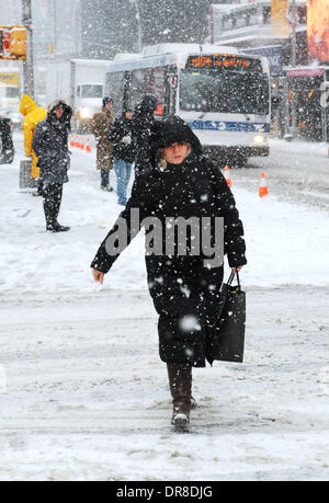 New York, NY, USA. 21st Jan, 2014. A woman walks in snowstorm across a street near the Times Square in New York - Stock Photo