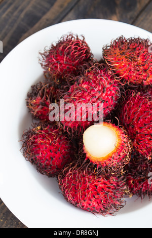 Rambutan is a tropical sweet and sour, white, translucent fruit with a red leathery skin with hairy protuberances. - Stock Photo