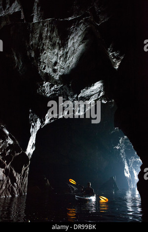 Sea kayaker in a cave beneath the Slieve League cliffs, County Donegal, Ireland. - Stock Photo