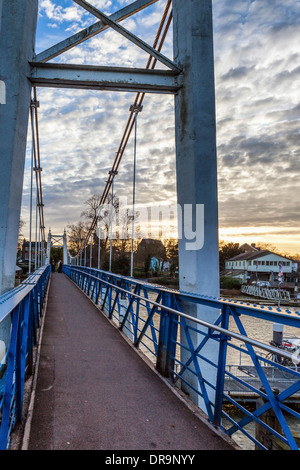 Pedestrian bridge and walkway over the river Thames against clouds and sunset at Teddington Lock and Weir, Greater - Stock Photo
