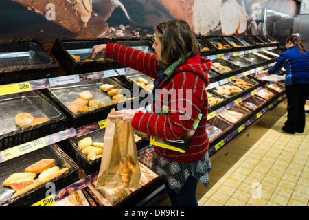A middle aged woman buying fresh baked in-store croissants and other bakery products in Lidl supermarket, UK - Stock Photo