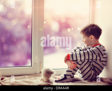 cute little boy sitting on the windowsill in the winter window - Stock Photo