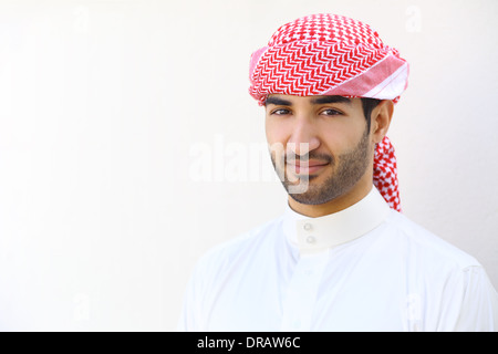 Portrait of an arab saudi man outdoor on a white wall - Stock Photo