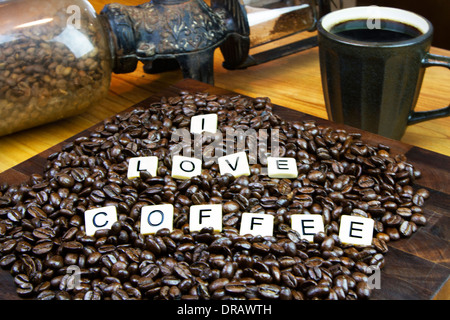 I LOVE COFFEE game tiles set in coffee beans with a cup of coffee and a grinder in the background - Stock Photo