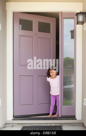 Little girl with open door at the entrance of house