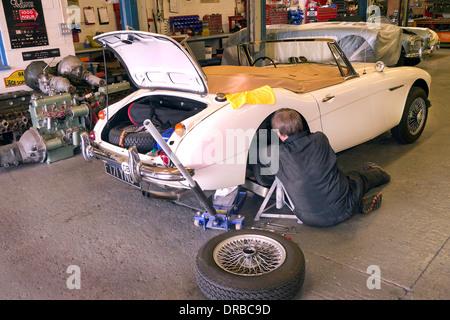 Classic car mechanic working on a Austin Healey 3000 MKIII in his workshop - Stock Photo
