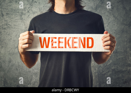 Man holding board with WEEKEND title. Interlude concept. - Stock Photo