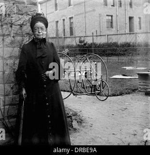 Portrait of a woman in period dress in front of an early two-seat tricycle. Photographed around 1900.