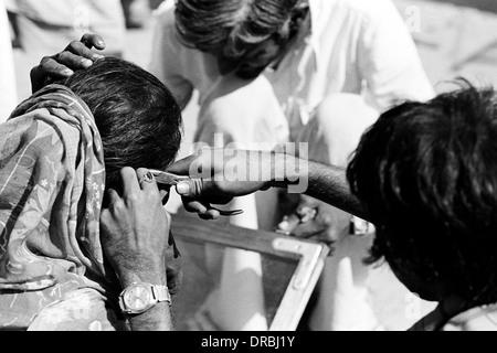 Man fixing woman ear ring with plier, Vautha fair, Gujarat, India, 1983 - Stock Photo