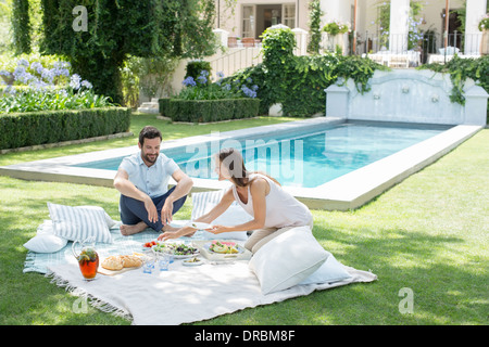 Couple enjoying picnic by pool - Stock Photo