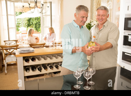 Senior me looking at wine bottle in kitchen - Stock Photo