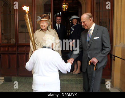 Britain's Queen Elizabeth II looks at the Olympic Flame as the Duke of Edinburgh shakes hands with Torchbearer 073 Gina Macgregor at Windsor Castle, Berkshire.      Windsor, Berkshire - 10.07.12 Stock Photo