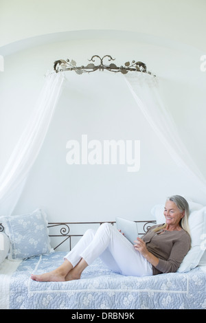 Senior woman with digital tablet relaxing in daybed - Stock Photo