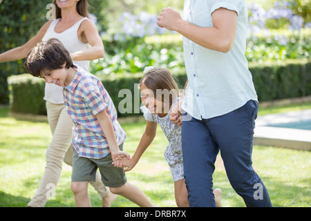 Family holding hands and running in backyard - Stock Photo