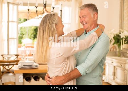 Senior couple hugging in kitchen - Stock Photo