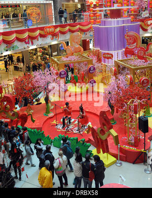 Hong Kong, China. 23rd Jan, 2014. Customers watch performance on a stage amid New Year decorations at a shopping - Stock Photo