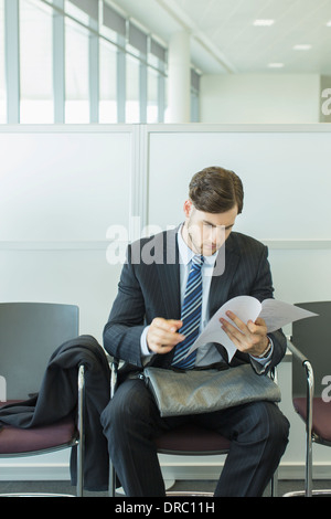 Businessman looking at resume in waiting area - Stock Photo